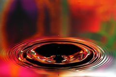 Water drops splash. Red and yellow ripples, reflections on surface.  royalty free stock photo