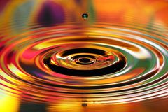 Water drops splash. Red and yellow ripples, reflections on surface.  stock photos