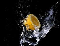 Water drops splashing onto a lemon. On black stock photos