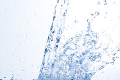 Water, drops, sprays, splashes, stream, flow, abstraction, minim. Flowing water, drops, sprays, splashes on a neutral background, studio light, abstraction Stock Image