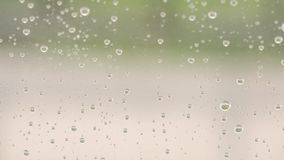 Water drops of storm rain on window with strong wind. Large and small drops of rain and small snow fly past window, flow down transparent surface, drop stock video footage