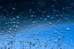 Water drops texture. Blue water drops spread on a window after a rainy day Royalty Free Stock Image