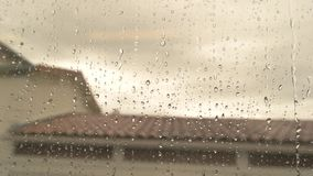 Water drops on train window. Blurred rooftop and sky. Bid farewell to home stock video footage