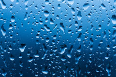 Water drops on a window. Blue Stock Images