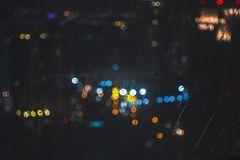 Water drops on window with bokeh light. Background of the night city view Royalty Free Stock Image