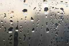 Water drops on window glass. Fine and large water drops on morning window glass Stock Images