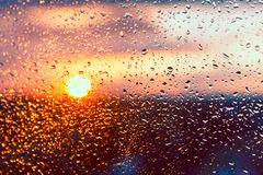 Water drops on a window glass after the rain. The sky with clouds and sun on background Stock Photography