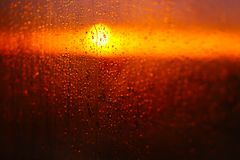 Water drops on a window glass after the rain. The sky with clouds and sun on background. Royalty Free Stock Images