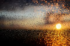 Water drops on a window glass after the rain. The sky with clouds and sunlight on background Royalty Free Stock Images