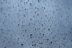 Water drops on the window. Great water drops on a window focus on the middle with blue background Royalty Free Stock Image