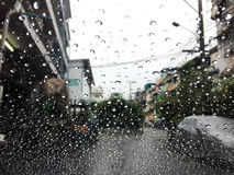 Water drops on a window in the heavy rain. Water drops on a window in the rain. View of car on the street Stock Photography