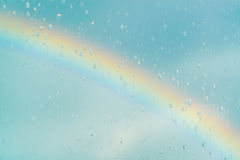 Water drops on a window with the rainbow in the background. Water drops on a window with the rainbow on the blue sky in the background Royalty Free Stock Photography