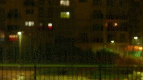 Water drops on window while raining outside. Defocused multistorey buildings with window lighting and activity in the background. stock video footage