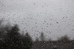 Water drops on window. With blurred trees and house in background royalty free stock photo