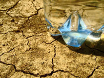 Water on dry ground. A water bottle on a dry and thirsty ground Royalty Free Stock Image