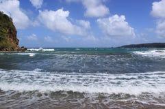 Water en golven. Zwart zandstrand, Dominica, Caraïbische Eilanden Royalty-vrije Stock Foto's