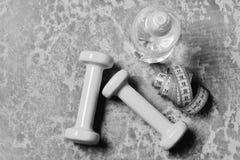 Water en maatregelenband dichtbij plastiek barbells Training en verfrissing royalty-vrije stock foto