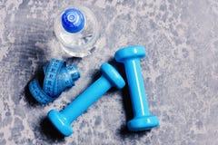 Water en maatregelenband dichtbij plastiek barbells Training en verfrissing royalty-vrije stock foto's
