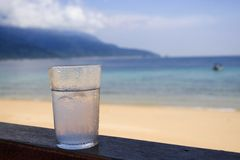 Water Everywhere. Shot of ice cold drink with sea and mountain and cloud as background. Water is everywhere, in the glass, sea and clouds royalty free stock images