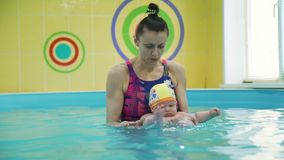 Water exercises for infant in the paddling pool. With swimming instructor in slow motion. Hardening and disease prevention. Healthy lifestyle for a child. Baby stock video