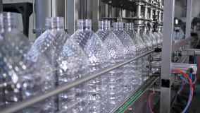 Water factory, bottling pure spring water into plastic bottles at plant. Close-up stock footage