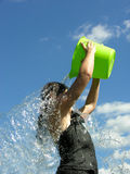 Water-fall. A young girl pours water from a bucket over her head Stock Photo