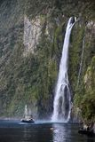 Water fall and boat in the Milford Sound Stock Photo