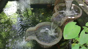 Water fall brown bowl decorated in garden pond stock footage