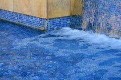 Water Fall Feature. Blue tiles under the water fall bringing a cool peaceful feeling Royalty Free Stock Image