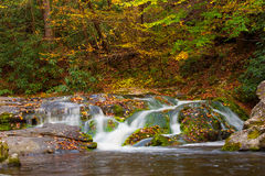 Water fall. Silk-like water flow over the rocks and colored leaves Royalty Free Stock Photos