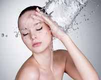 Water falling on beautiful woman face stock photography