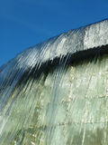 Water Falling Fountain. Water spilling over concrete fountain against bright blue sky Royalty Free Stock Images