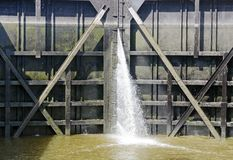 Water falling through a gap of an old sluice gate Stock Photo