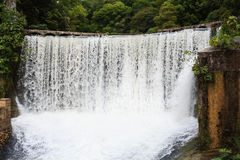 Water falling from old power plant dam in New Athos Stock Photos