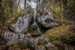 Water falling between two large rocks in autumn forest at Myrafälle stock image