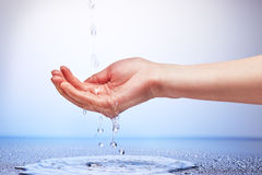 Water falling in women's hand Stock Photography