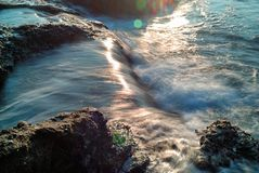 Water falls coming off the tide pools as the currents ebb and flow. Waterfalls occur in and out of the Pacific Ocean, flowing down the rock formations that are stock photo