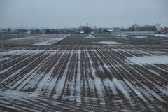 Water on the farm fields after harvesting with melting snow stock images