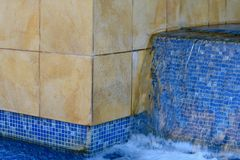Water Feature. Blue tiles under the water fall. Bringing some peaceful feeling Stock Image
