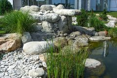 Natural stone waterfall cascade in pond design. Water feature design, two-tiered patio pond built with stone boulders Royalty Free Stock Photography