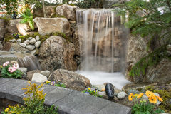 Water Feature with pond and flowers. Water feature with rocks, waterfall, flowers and a pond with a slow shutter to capture the motion of the water royalty free stock photos