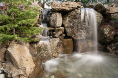 Water Feature with pond. Water feature with rocks, waterfall and pond with a slow shutter to capture the motion of the water stock image
