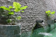 Water feature with a rockwall. Brickwall water feature with pond and water sprout royalty free stock images