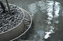 Water Feature Steel Edge. Modern double steel edge detail of pebble stone planter on water feature within contemporary building. Ripple effect of water surface stock image