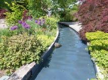 Water feature. Stream flowing through Ornamental garden Stock Photos