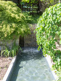 Water feature. Waterfall in Ornamental garden and park Stock Images