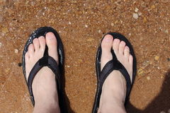 Water on Feet. A close up view of clear water running over two feet in black sandles Royalty Free Stock Photo