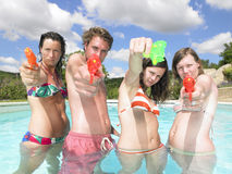 Water fight. Friends playing with water guns in pool Stock Photography