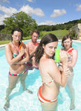 Water fight. Friends playing with water guns in pool Royalty Free Stock Photography