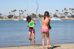 Water Fight. Two girls having a water fight at the beach Stock Photos